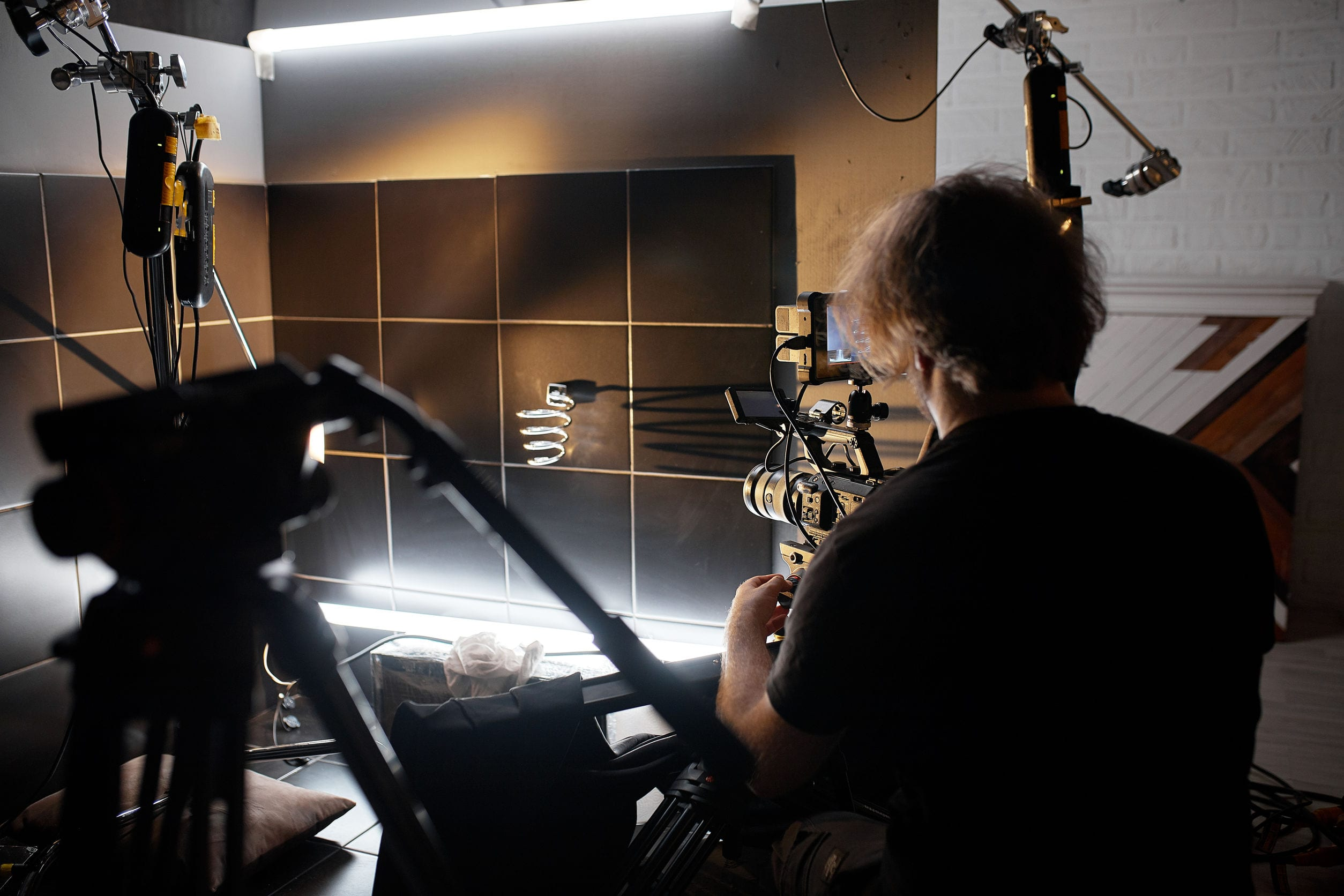 Video production backstage. Behind the scenes of creating video content, a professional team of cameramen with a director filming commercial ads. Video content creation, video creation industry, Low key, selective focus, film graine.